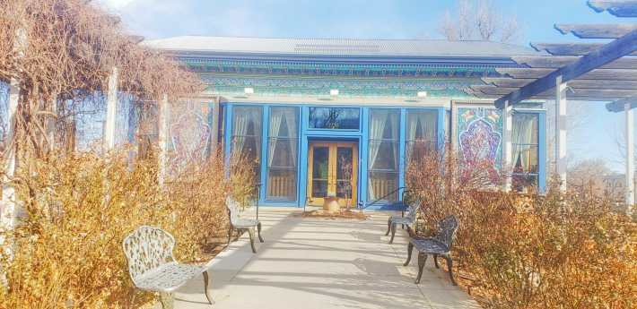Front entrance of a building with bright blue trim work and intricate, colorful tile work
