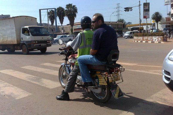 Tourist on a boda boda ride in Kampala: How To Travel in Uganda On a Budget