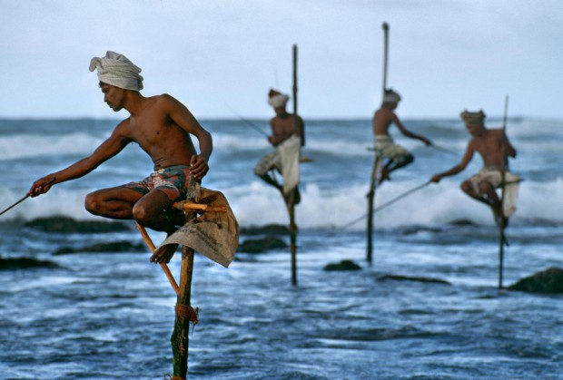 """Weligama, South coast, Sri Lanka, 1995.""""Fishermen along the southern coast of Sri Lanka cast their lines in the traditional way atop poles so they can work in shallow water without disturbing the fish.""""  - George Eastman HouseThe theatrical stage would not offer a finer gesture, nor a more equisite doubling between the near and the far, than does this picture.  McCurry captures the beauty of a cultural tradition and with it a natural choreography.  This image also preserves a practice now essentially lost to technology, having all but disappeared in the intervening years since the photograph was made.  -Anthony Bannon Magnum Photos, NYC5948; MCS1995006K200, Phaidon, 55, South Southeast, Iconic Images, final book_iconic"""