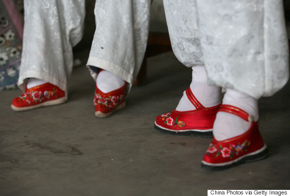 """TONGHAI COUNTY, CHINA - APRIL 2: (CHINA OUT) Members of the Bound Feet Women Dancing Team, dance on their """"Three Cuns Golden Lotus"""" shoes at Liuyi Village on April 2, 2007 in Tonghai County of Yunnan Province, China. """"Three Cuns Golden Lotus"""" is a term used to describe ancient Chinese women's bound feet, in which three """"cuns"""" are about 3.39 inches. Liuyi Village is known as the """"Bound Feet Women Village,"""" where over 100 female senior citizens with bound feet and over the age of 70 live. The Chinese custom of foot binding under the feudalization, which started during the Tang Dynasty (AD 618-907) , was discontinued in the early 20th century. (Photo by China Photos/Getty Images)"""
