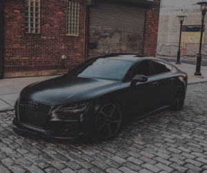 Black Audi car on a cobblestone road in front of a brick building