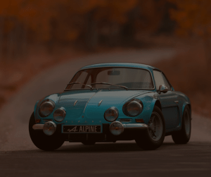 Small blue car on a road in fall