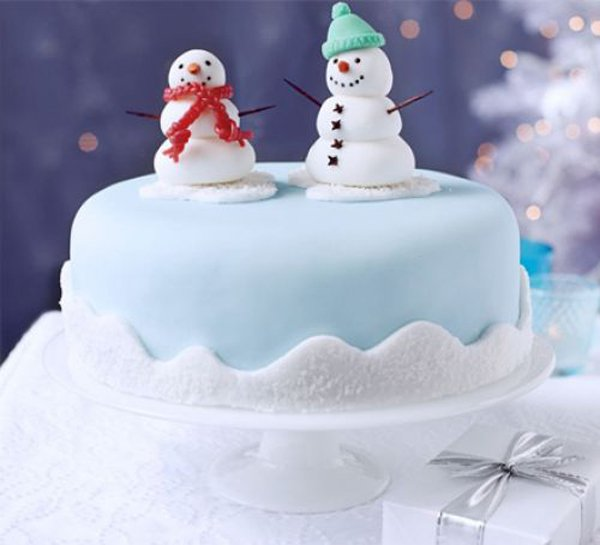 A very cute Christmas cake with a snowman couple on top. The cake is designed to look like a snow yard with two cute snowmen on top that looks like a cute couple under the snow.