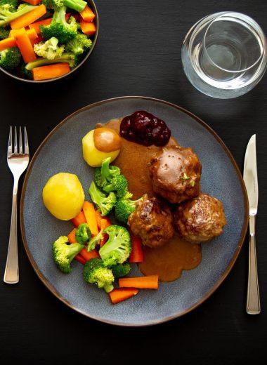En tallerken kjøttkaker i brun saus med potet og gulrot