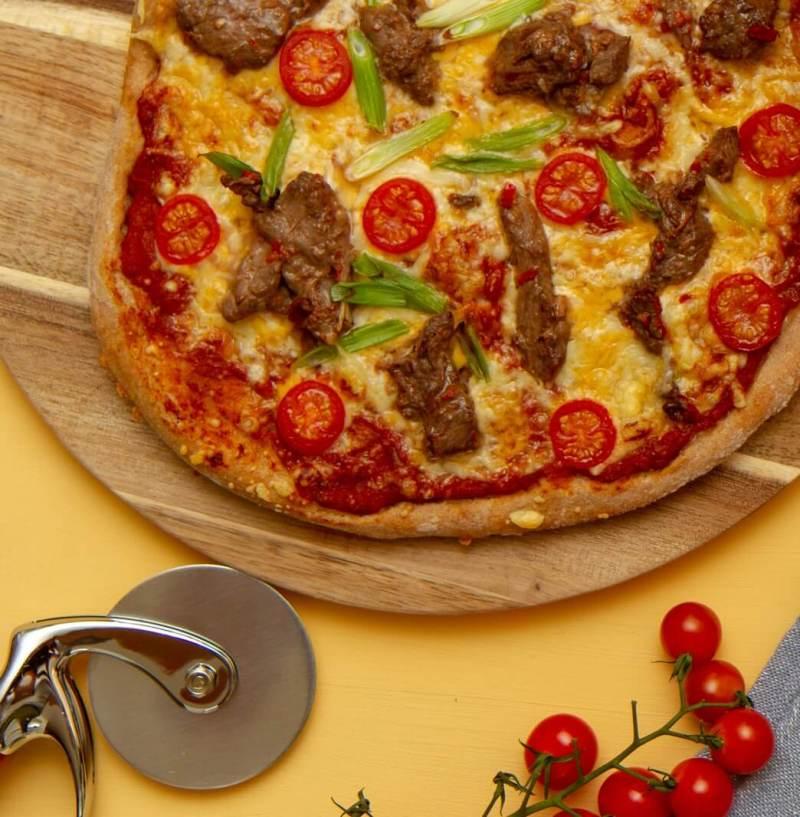 Pizza med biffstrimler og tomater