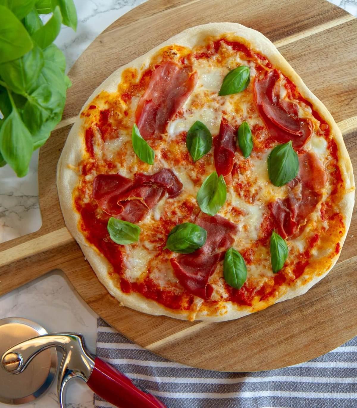 Pizza med med spekeskinke og basilikum