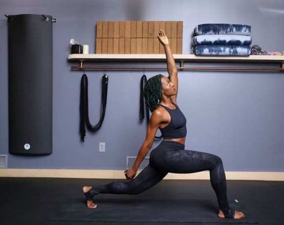 Photo of Amina Daniels, owner of Detroit fitness studio Live Cycle Delight, in yoga pose.