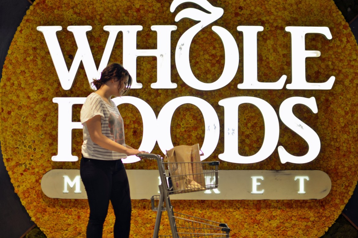 Person shopping at Whole Foods in front of store sign.