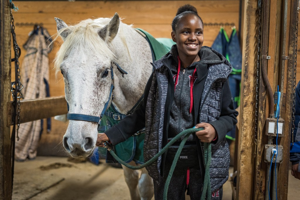 Detroit student leading horse at after-school program.