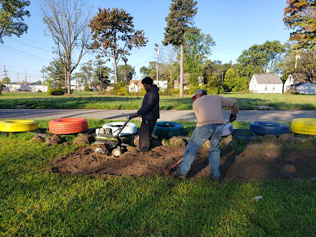 detroit farmers working on making a new area of grass into a garden