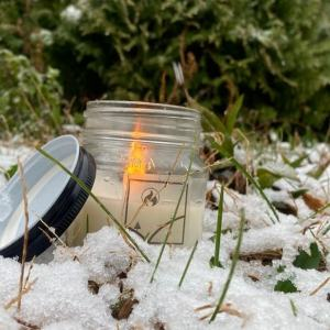 Kombeat, lit candle set in grass that is lightly covered by snow