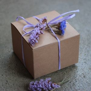 Motor City Soap Company, brown gift box tied in a bow with purple string and purple flowers tucked into the bow.