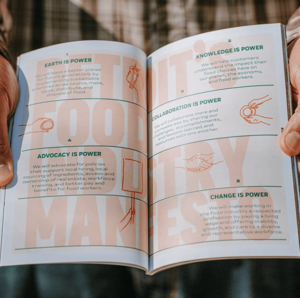 Image, person holding a book open to Detroit's Food Industry Manifesto