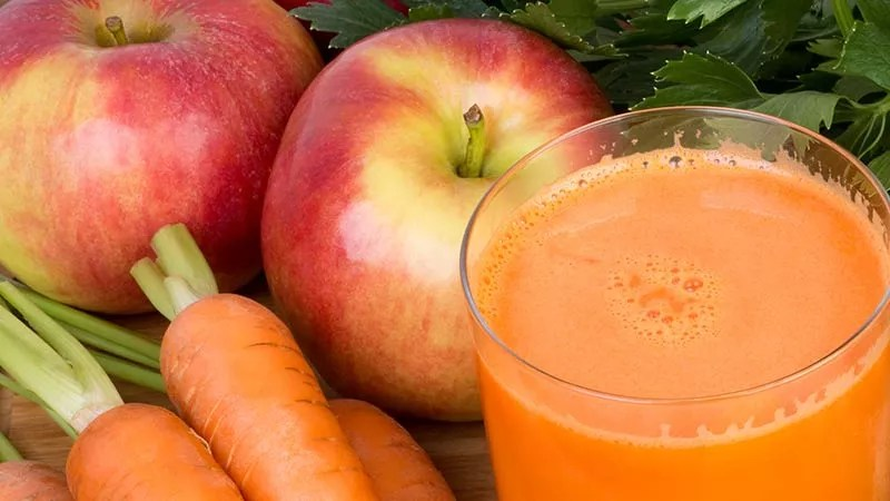 Best Weight Loss Juice Recipe - orange colored juice on a timber table next to whole red apples, carrots with the tops on but trimmed, and celery leaves
