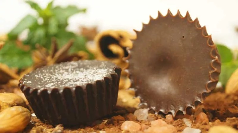 How to Stop Sugar Addiction - picture of homemade chocolate on a timber chopping board surrounded by whole almonds with the skin on, Himalayan rock salt, ground cinnamon and peppermint leaves blurred out in the background. The chocolate was set in a cup cake patty pan which has given it a crimped edge outline