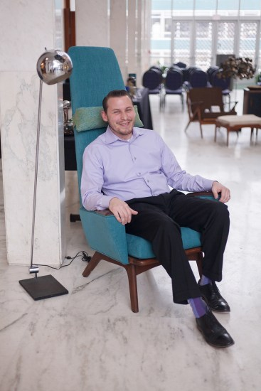 Block Auction House Founder, Aaron Siepierski. In the lobby of McGregor Center seated in an Adrian Pearsall Slim Jim Lounge Chair with a Robert Sonneman Floor Lamp