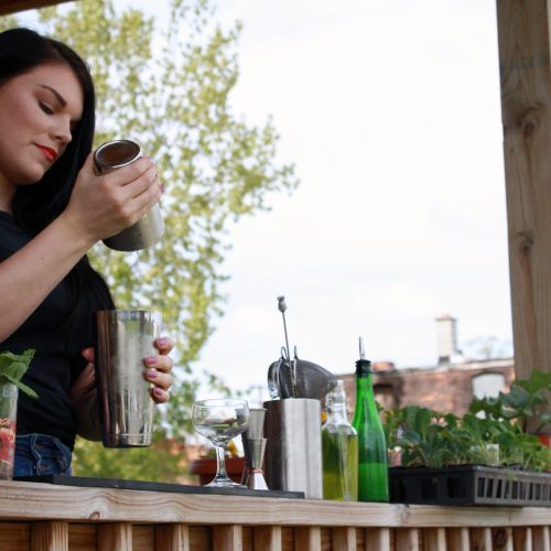 HOSPITALITY BARTENDER ALLISON EVERITT SHAKING A COCKTAIL ON THE FRONT PORCH OF HER DETROIT HOME
