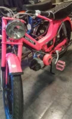A pink Puch Maxi moped with matching pink pedals.