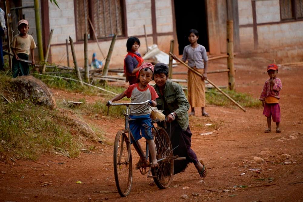 Gutt lærer å sykle i en landsby i Myanmar