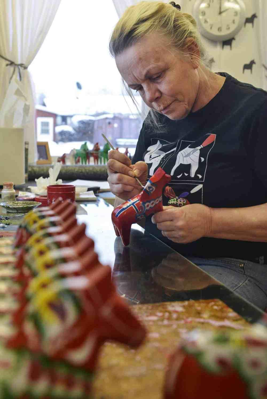 Kvinne maler dalahest i Nusnäs i Sverige