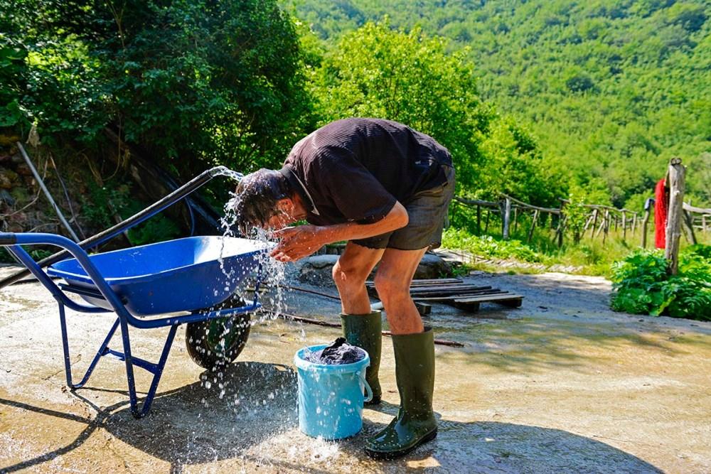 Zoran tar en kattevask med vann fra bøtta
