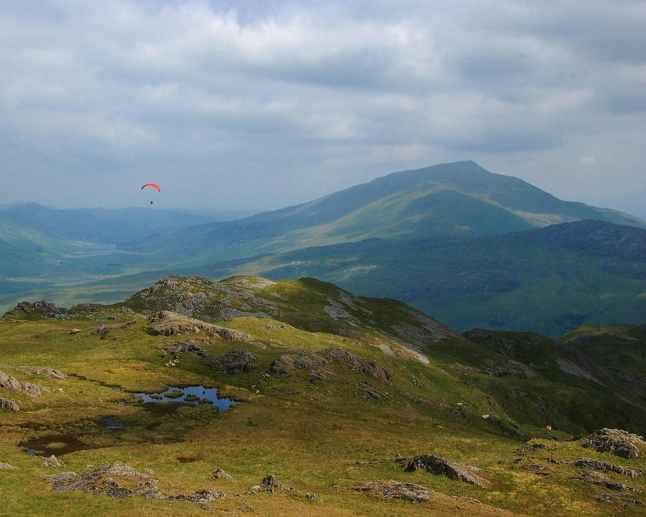 Hangglider over fjellene i Snowdonia National Park i Wales