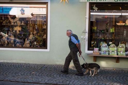 Mann går tur med hunden i tysk alpeby