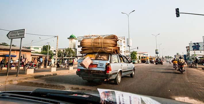 Svært full Peugeot kjører i trafikken i Cotonou