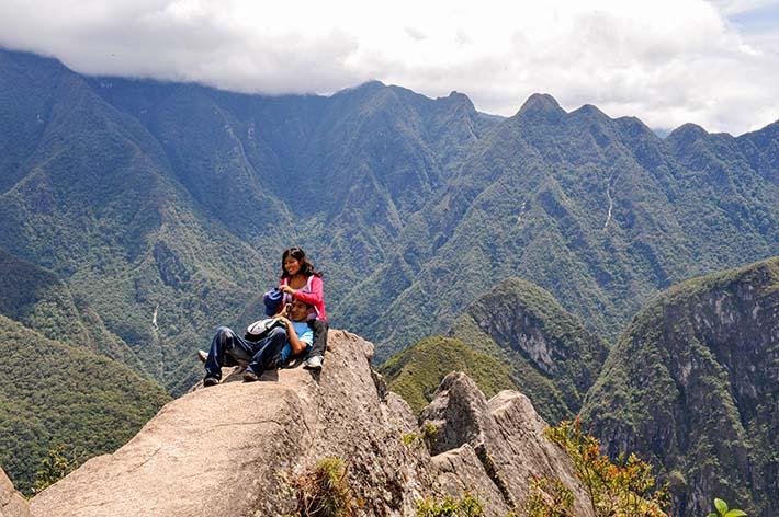 Kjærestepar balanserer på fjellegg på Huayna Picchu