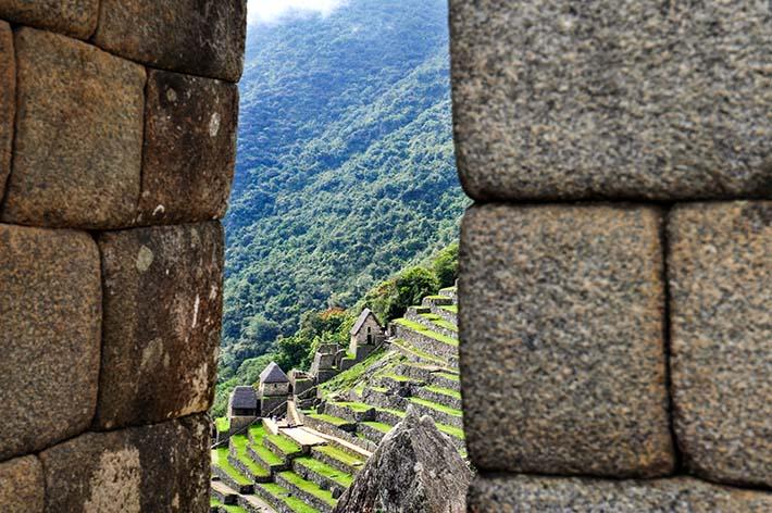 Terrasser i Machu Picchu sett gjennom et vindu.