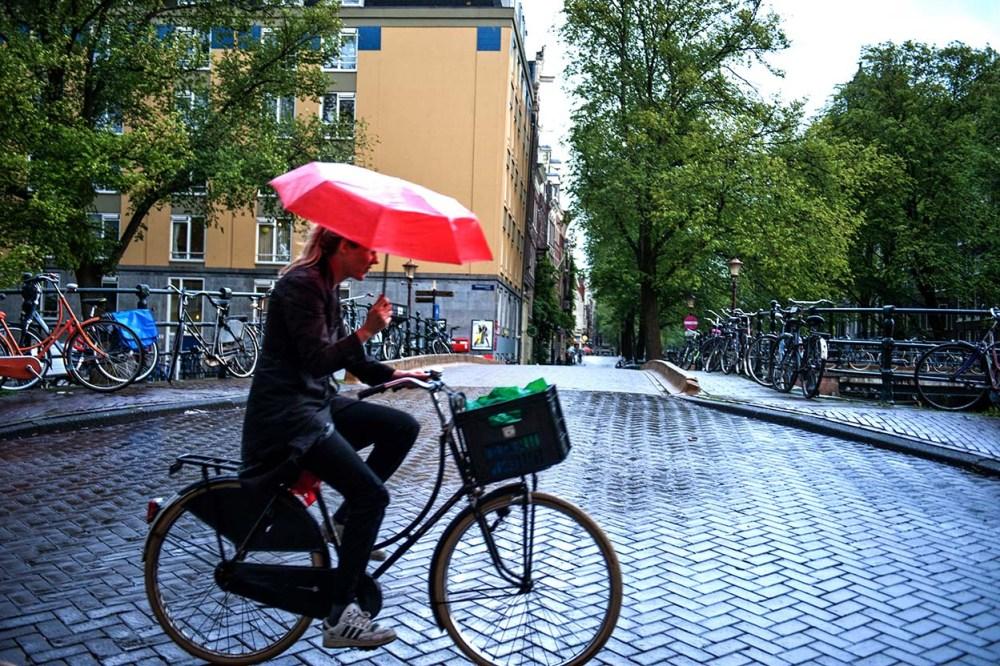 Kvinne sykler med paraply i Amsterdam