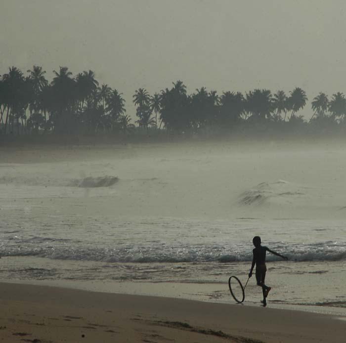 Barn leker med hjul og pinne på en strand i Vest-Afrika