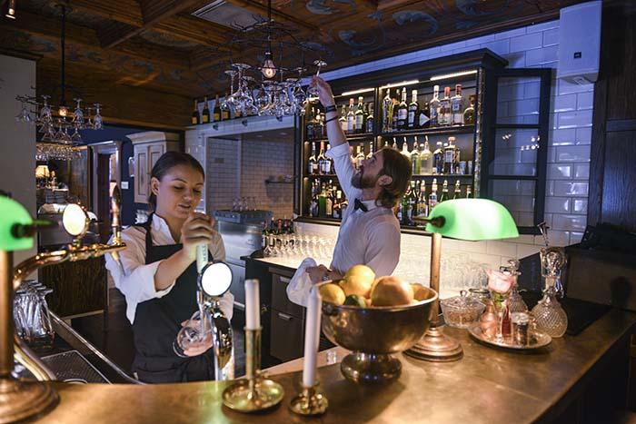 To bartendere jobber i lobbybaren i Hotel Åregården