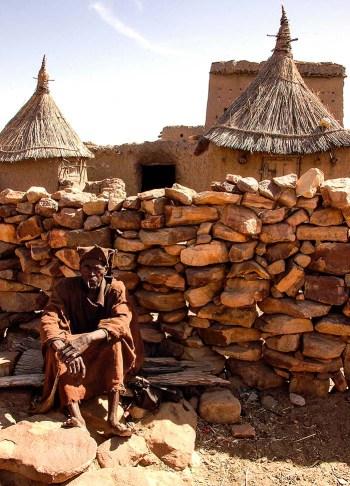 Mann sitter foran mur i Dogon