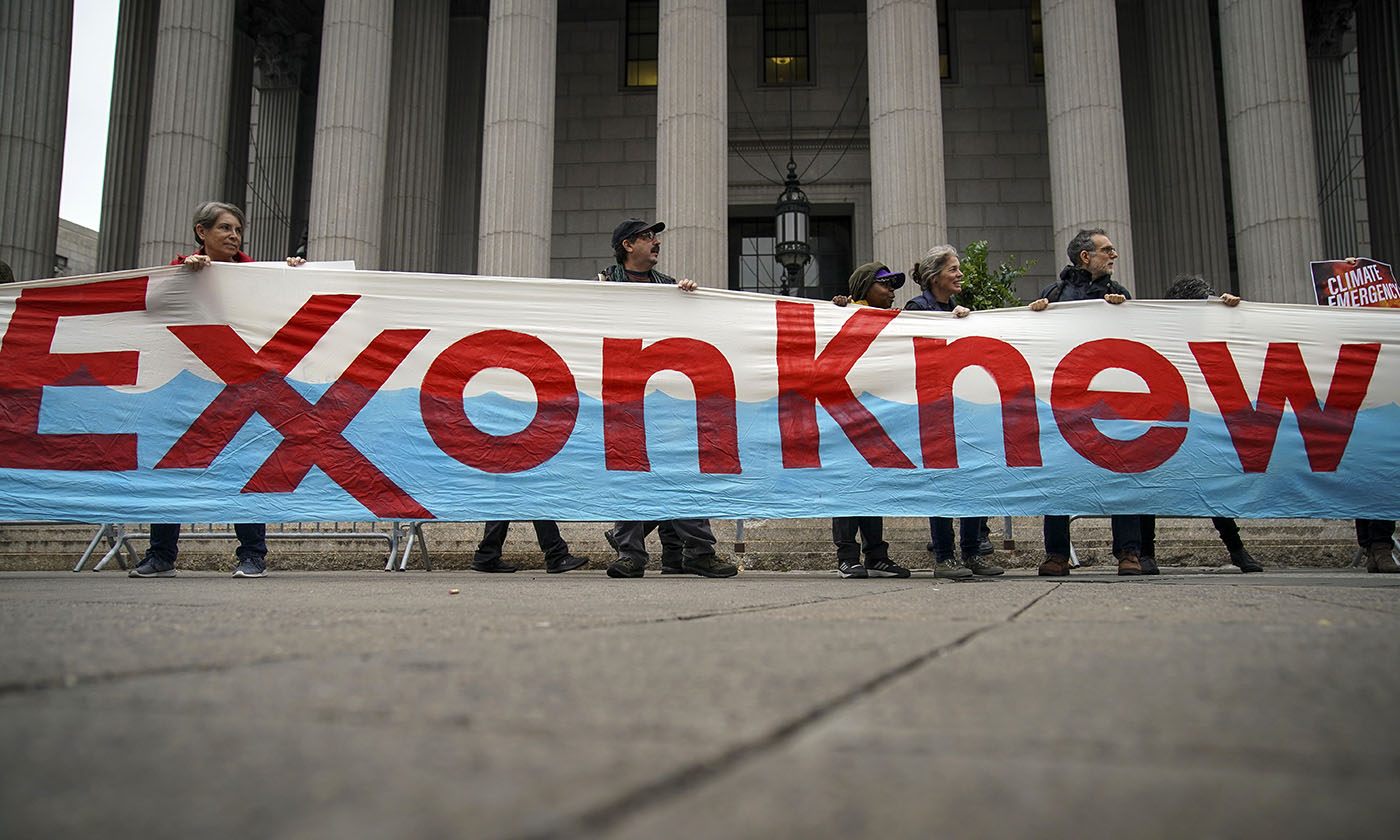protestors hold up a sign that says exxon knew