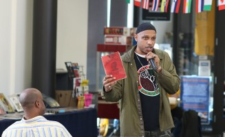 Khalid giving a lecture on the origins of the stereotypes of Black inferiority using Chase Carroll's The Negro a Beast or in the Image of God. (Portland Community College