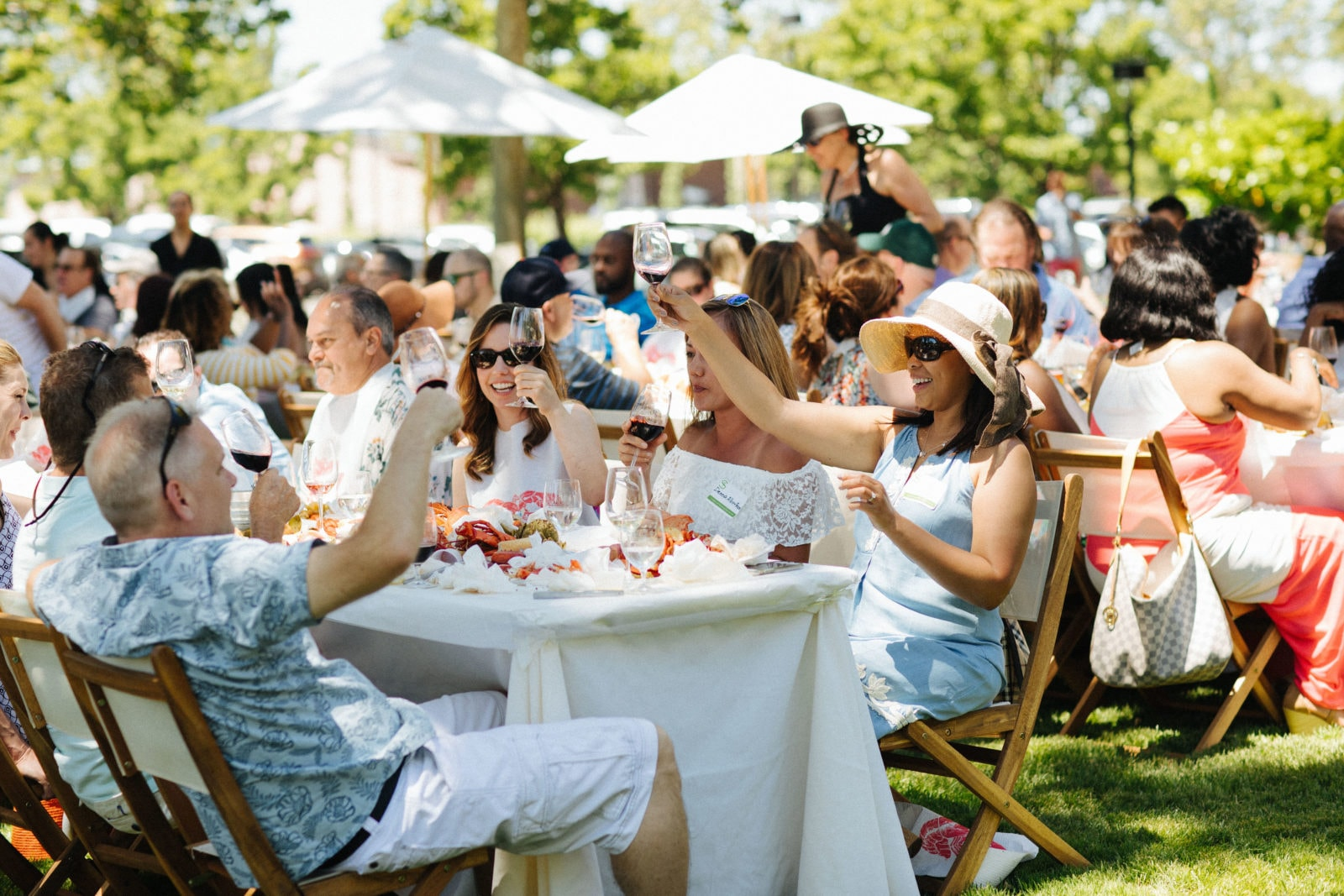 Wine club members raising their glasses with St. Supéry wine at our annual Spring Fling lobster boil.