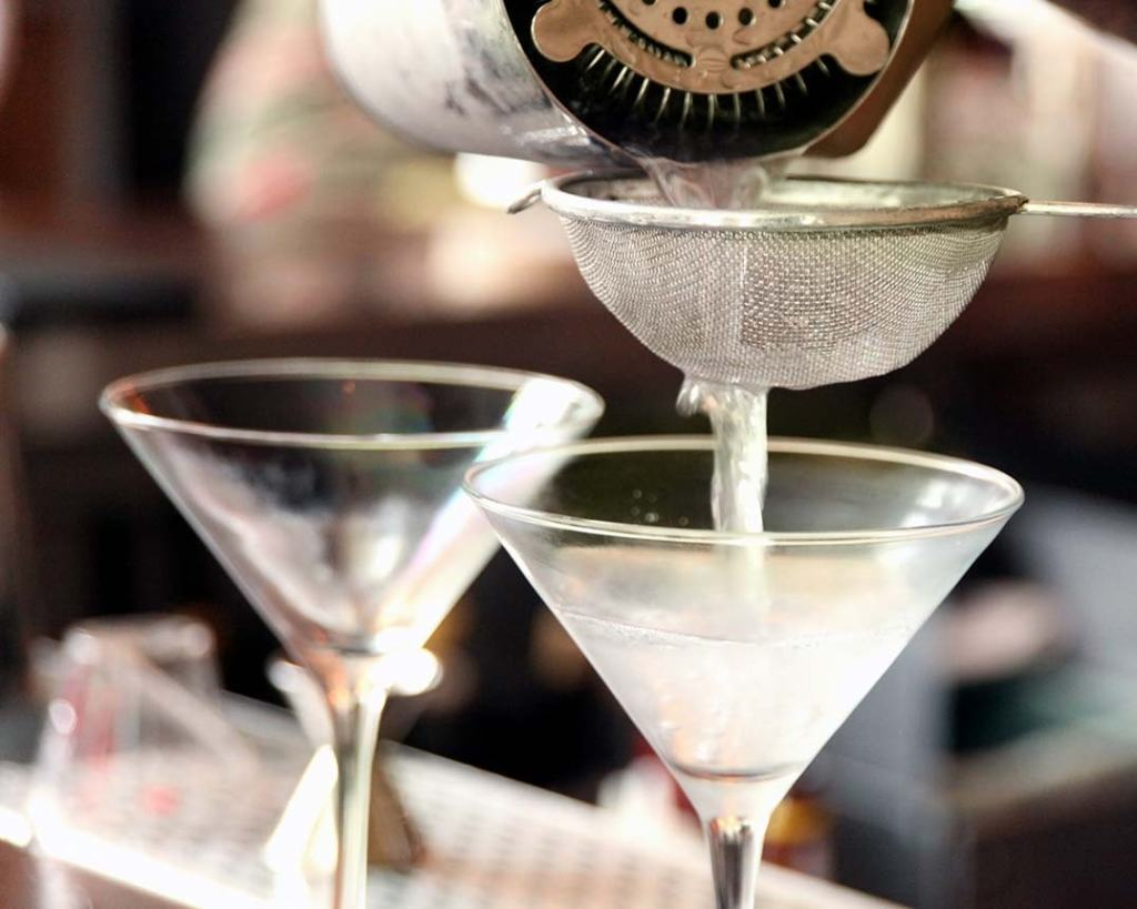 pouring St. Supéry Thunderball Cocktail through fine mesh sieve into martini glass