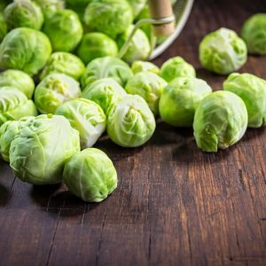 Close-up of fresh organic brussels sprouts (Brassica oleracea), rolling out of their strainer basket on a rustic wood table