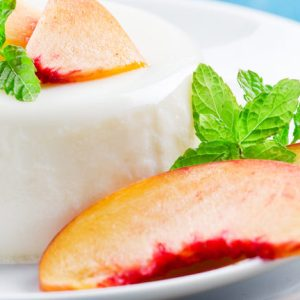 Close up photograph of a panna cotta dessert with peaches