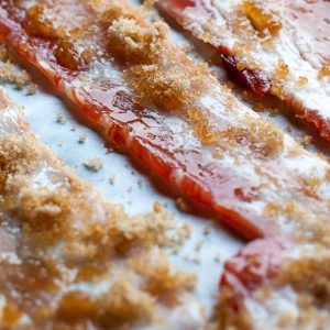 Strips of bacon with brown sugar on parchment, perfect pairing with cabernet sauvignon