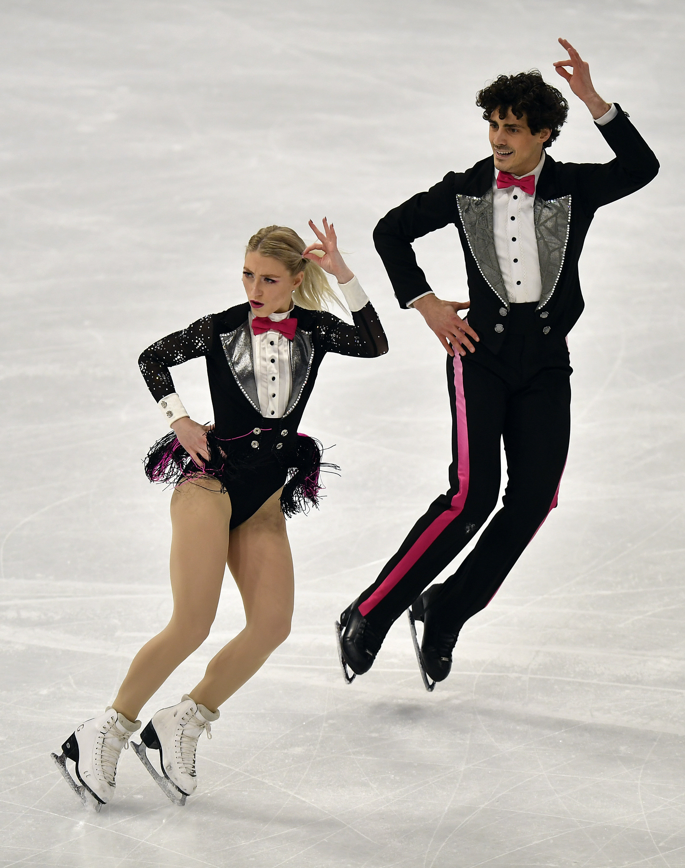 Two ice dancers perform side by side
