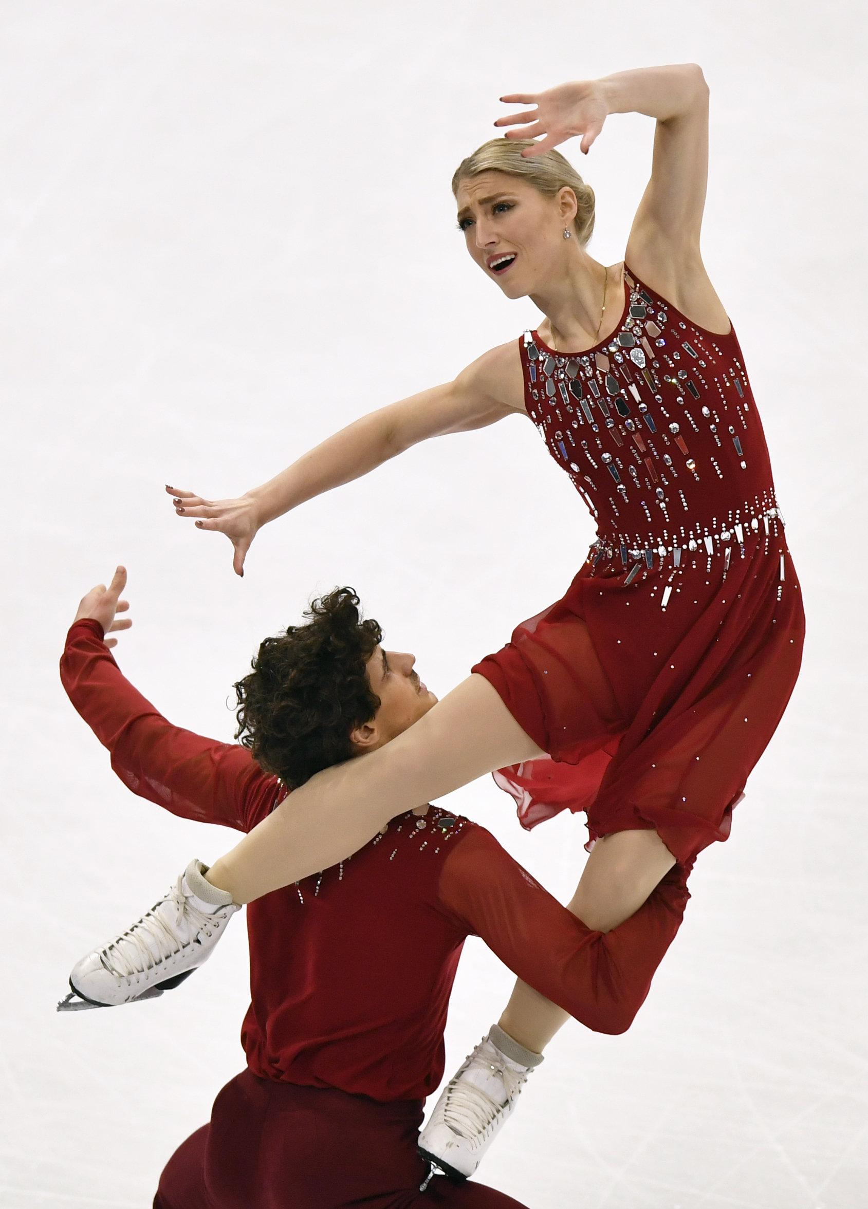 Male ice dancer lifts female partner