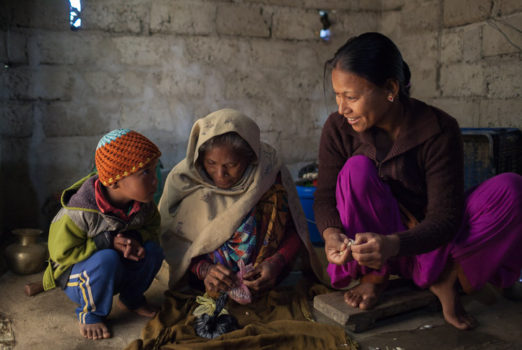 November 19, 2013 - Binauna village, Banke (Nepal). Jharana Kumari Tharu, her son and her mother-in-law, 70-year-old Ashpati Tharu, prepare lunch for the rest of the family. Jharana is a female community health volunteer in Binauna village, in Nepal's Banke District where she works encouraging better health behaviors among Nepal's underserved populations, including expectant and new mothers. Her mother-in-law also volunteered in the same role for 21 years and encouraged Jharana to take up the work.