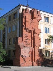 """Foto atual do prédio de apartamentos onde Pavlov e seus homens lutaram. No monumento ao lado, pode-se ler: """"Nesta construção uniram-se feitos heroicos de guerra e de trabalho. Nós iremos defender e reconstruir você, querida Stalingrado!"""" (Fonte: Wikicommons / Autor: Andrey Volykhov)"""