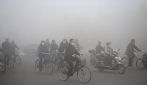 Ciclistas no meio de um nevoeiro de fumaça, na China.