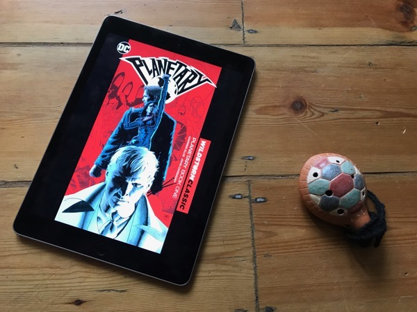 An iPad showing the cover of the first 'Planetary' collection, on a wooden floor, alongside an ocarina