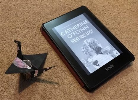 A Kindle showing the cover of Catherine O'Flynn's What Was Lost next to an origami bird
