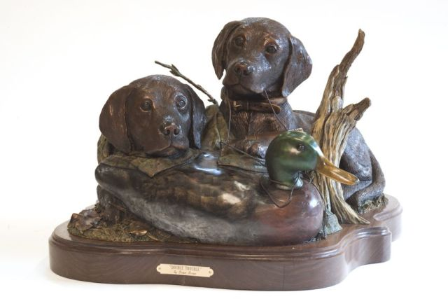 Puppies rest near a duck in the bronze sculpture 'Double Trouble'.