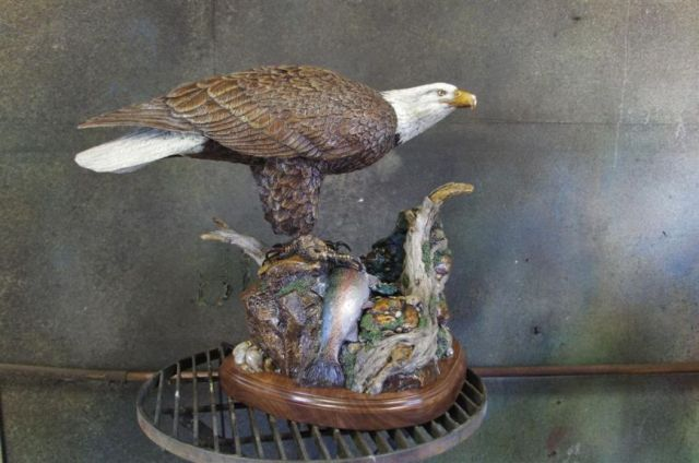 A bad eagle stands ready to eat a fish in the bronze fountain 'End of Spring'